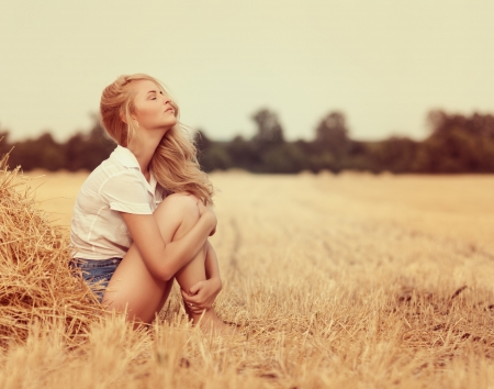 daydreaming: Attractive young woman near the stacks of straw