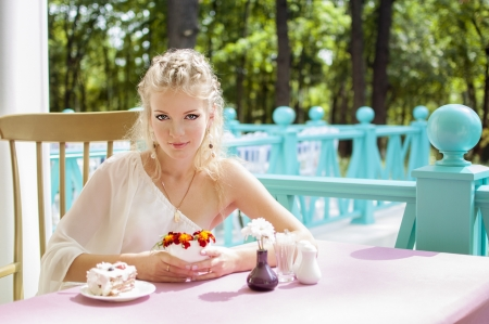 woman eating cake: Young woman dreams  Next to her is cake  Stock Photo