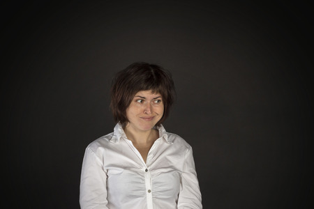 duplicitous: Portrait of young smiling woman on black background