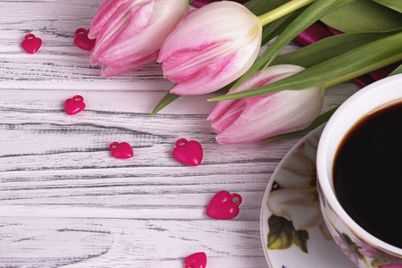 Valentines day elegant still life with tulip flowers cup of coffe marshmallows zephyr red heart shape sign on white wooden background