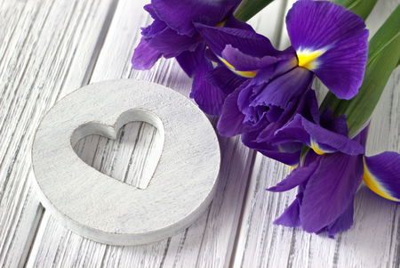 Still life with heart sign iris flowers on white wooden background. Wedding. Valentines Day greeting card concept.