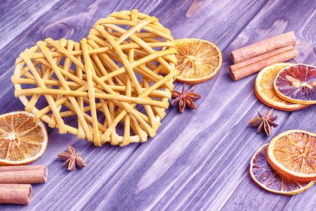 Beige wicker heart on a brown wooden background, vintage