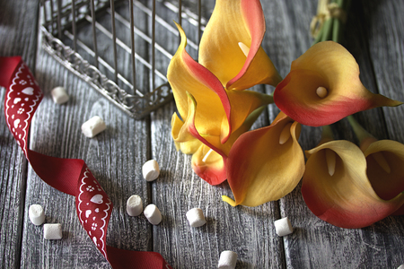 orange yellow calla lilies with red ribbon and white marshmallows on wooden gray background. Stock Photo