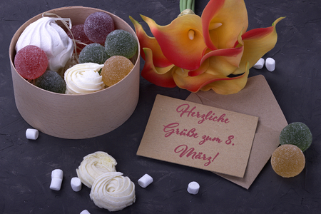 bouquet of red yellow callas marshmallows marmalade in a round box and envelope on gray concrete background lettering Kind regards to the 8th March German Reklamní fotografie