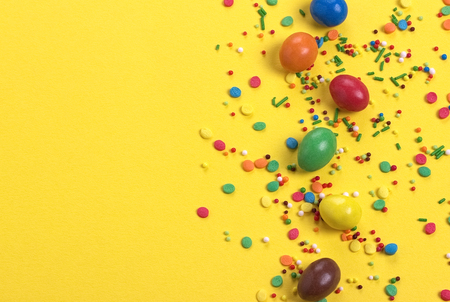 Easter chocolate egg with colorful explosion of candies and sweets on yellow colored background