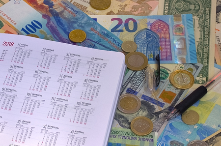 calendar on euro and dollar bills, calculator, ink pen and coin money background. Stock Photo