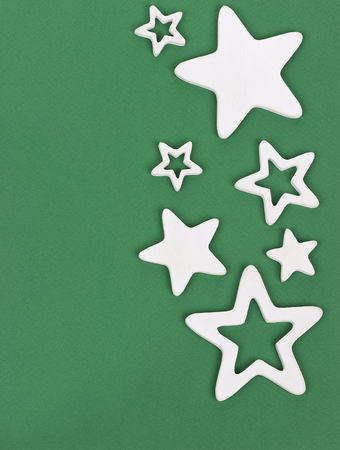 estrellas cinco puntas: White five-pointed wooden stars on green cardboard