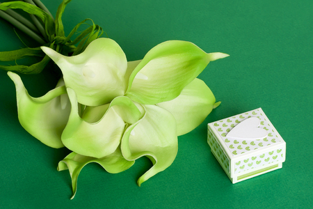 Bouquet of green yellow calla lilies with gift box and white heart on green cardboard background