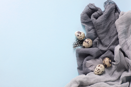 Easter decoration with quail eggs,gray fabric on blue background. Stock Photo