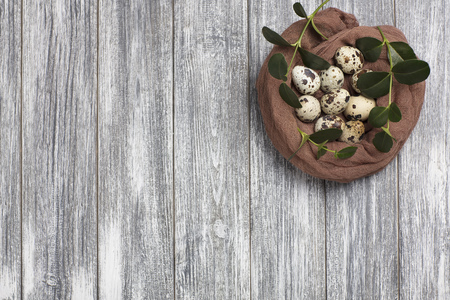 Easter decoration quail eggs with brown fabric on gray wooden background