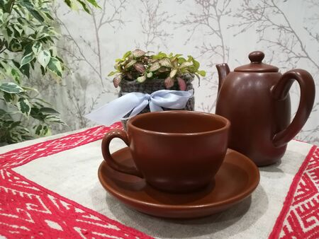 Tea cup, creamer and fittonia in a knitted pot on the table with linen embroidered napkin background Stockfoto