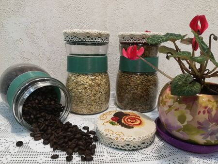 Glass jars with grains of coffee and cereal, embroidery on the lids, flower in a pot, light background, kitchen decoration