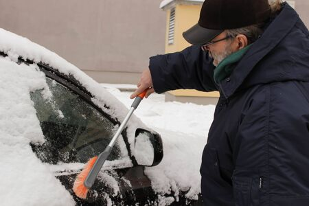 Transportation, winter, weather, people and vehicle concept - man cleaning snow from car with brush Stockfoto