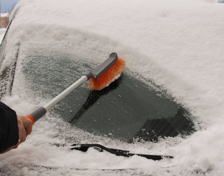 Transportation, winter, weather, people and vehicle concept - cleaning snow from car with brush Stockfoto