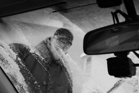 Transportation, winter, weather, people and vehicle concept - man cleaning snow from car with brush. View inside the car.