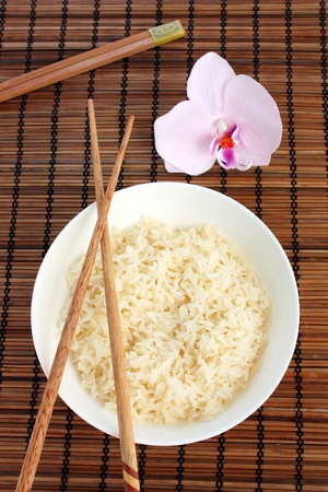thai orchid: Bowl of Chinese rice, chopsticks and an orchid, viewed from above. Stock Photo