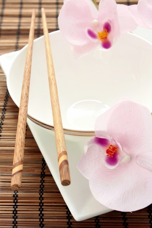 Chinese place setting with a white bowl and plate, chopsticks and orchids.