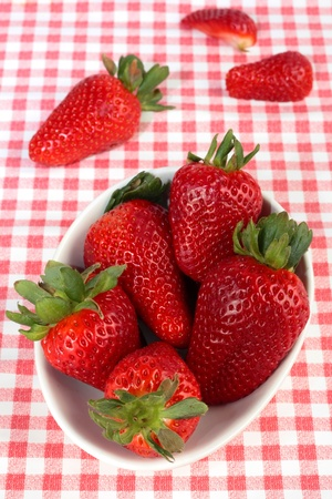 Strawberries in a bowl on a red checked table cloth