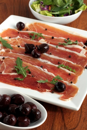 Plate of serrano ham with olives and side salad photo
