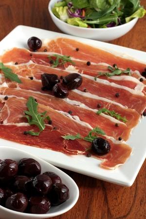 carnes y verduras: Plato de jam�n serrano con aceitunas y ensalada de cara Foto de archivo