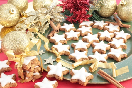 Star-shaped Christmas cinnamon cookies on a green plate. Decorated with gold, red and green Christmas decorations.