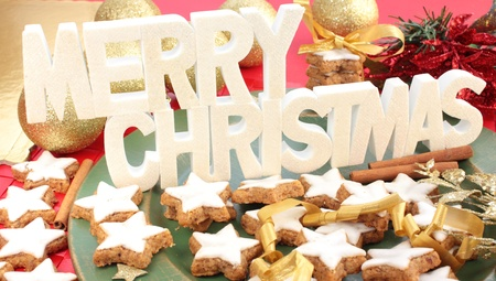 A white Merry Christmas sign above a plate of star-shaped cinnamon cookies. photo