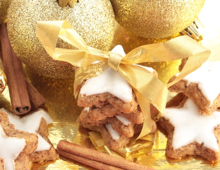 Star-shaped cinnamon cookies tied up to give as a gift. Decorated with gold Christmas decorations.