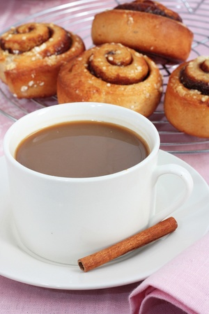 cinnamon swirl: A cup of coffee with freshly baked cinnamon rolls