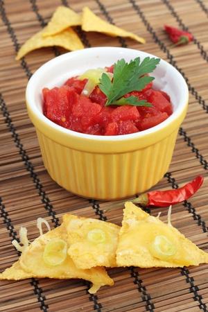 tortilla de maiz: Un tazón de salsa se sirve con nachos. Foto de archivo