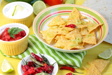 A bowl of nachos with dips including salsa and sour cream on a yellow background.