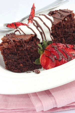 Chocolate brownies with cream and fresh strawberries Stock Photo