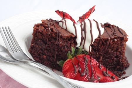 Chocolate brownies with cream and fresh strawberries Stock Photo