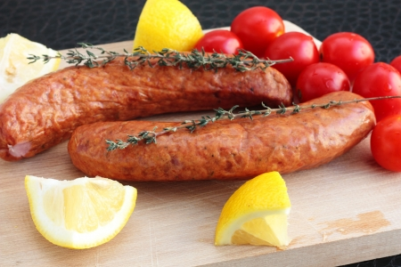 Sausages with cherry tomatoes, lemon and thyme Stock Photo