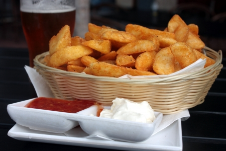 A basket of crispy potato wedges with sour cream and sweet chilli sauce dips and a beer photo
