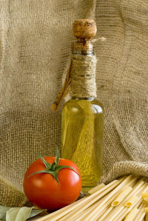 still life with bottle of olive oil and tomato photo