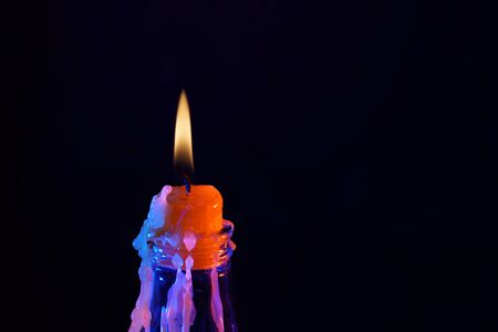 Candle after blowing out the flame photographed with colorful flashes in the studio Imagens