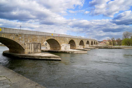 Stone bridge in Regensburg over the Danube with cathedral and Bruck Mandl Stock Photo