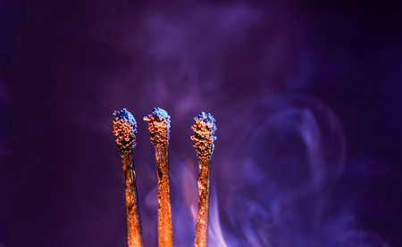 Lit matches and blown out in the studio photographed with colorful foils before the flashes