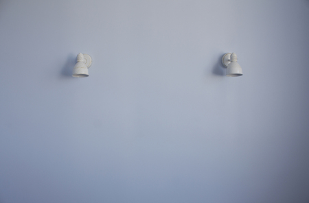 White patina metal lamps on a blue wall Stock Photo