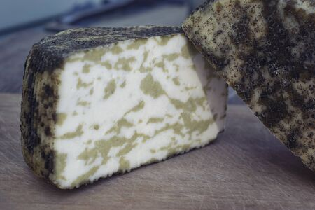 Craft cheese from cows and goats milk. Cheese head. Selective focus