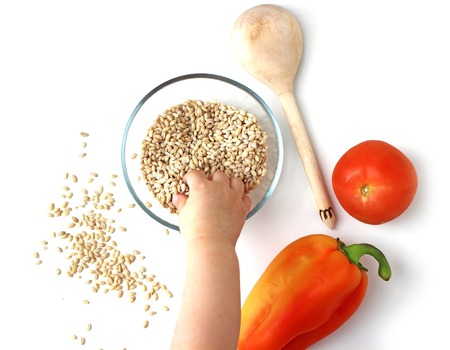 hand lay: Pearl Barley in a bowl with baby hand, flat lay view on white background, healthy eating concept, photo for lifestyle blogs Stock Photo