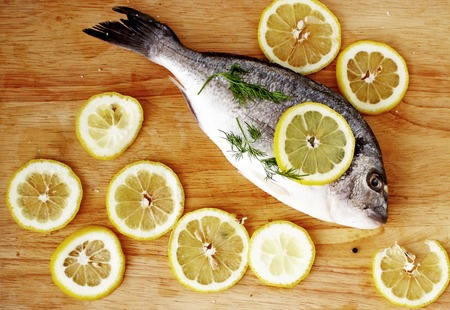 gilt head: Fresh gilt-head bream, dorado, with cutted lemon and dill on wooden board flat lay