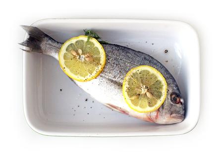 gilthead bream: Fresh gilt-head bream, dorado, with lemon in baking dish flat lay