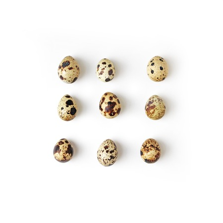 ordered: Uncooked ordered Quail eggs on white background top view, healthy food concept Stock Photo