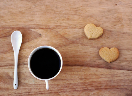 Coffee in porcelain cup and spoon and homemade heart-shaped cookies on wooden board top view, breakfast concept