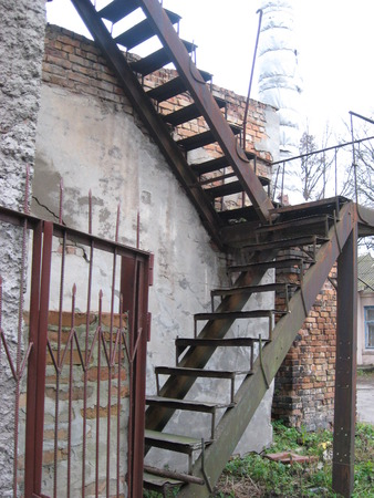 emergency stair: Rusty stairs near old  wall in the village