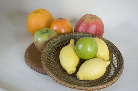 apples and oranges: Exotic fruits on a wicker plate.  lemon, lime and persimmon, apples oranges