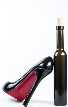 high heel shoe leaning on ice wine bottle Stock Photo