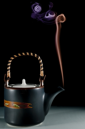 Smoking teapot with different colored smoked on back background Stock Photo - 17200818