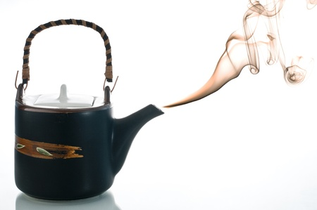 Smoking teapot with coloered smoke on white background photo